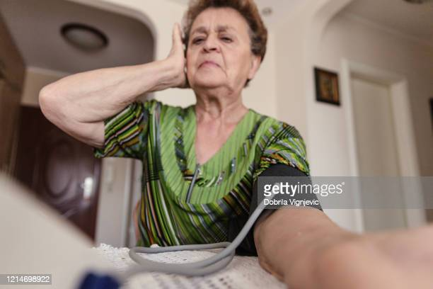 displeased old woman measuring blood pressure - cardiac arrhythmia stock pictures, royalty-free photos & images