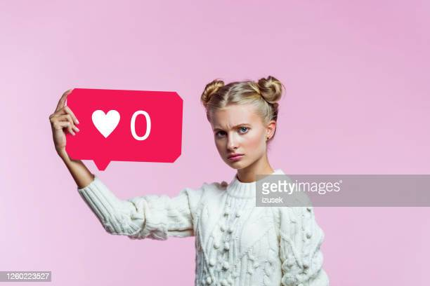 displeased teenege girl holding speech bubble in hand - social media stock pictures, royalty-free photos & images