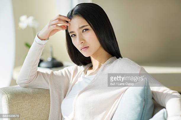 Displeased young woman sitting on sofa