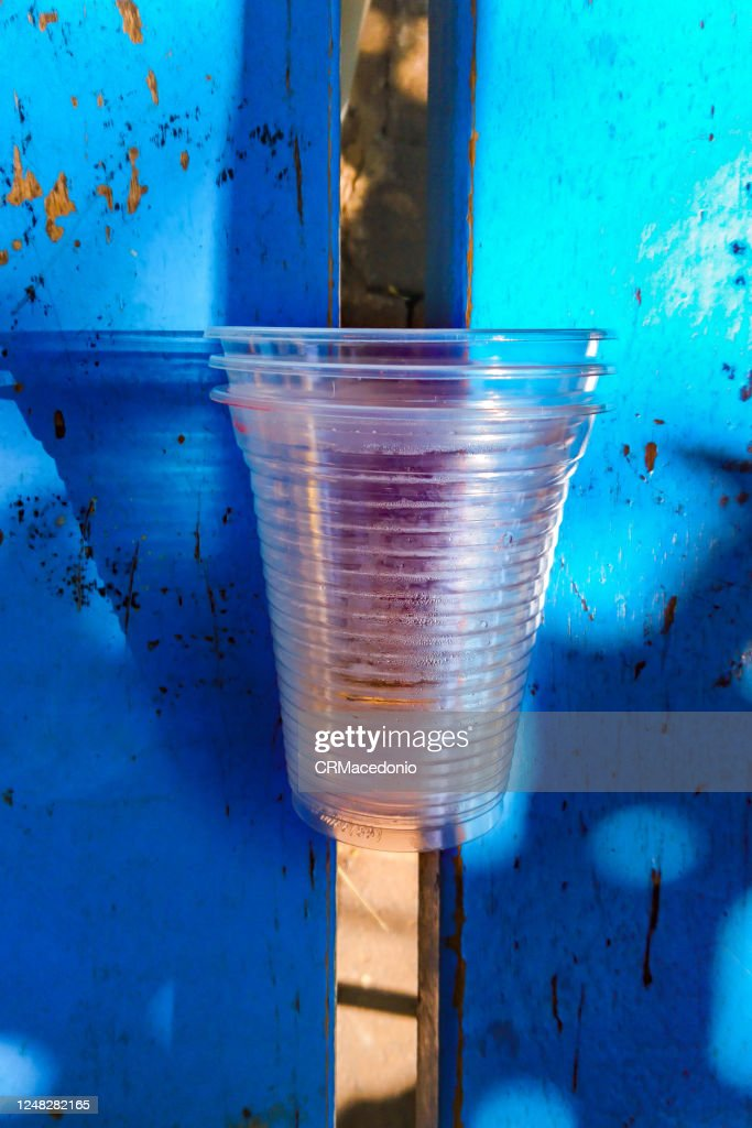Disposable clear plastic cups left in a public bench. : ストックフォト