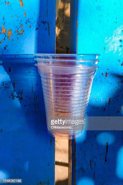disposable clear plastic cups left in a public bench. - crmacedonio stock pictures, royalty-free photos & images