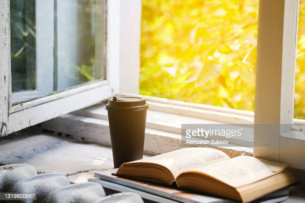 a disposable coffee cup or takeaway glass on an old wooden windowsill with an open window. there is an open book next to it. the concept of education, passing exams, preparing for university admission - college admission stock pictures, royalty-free photos & images