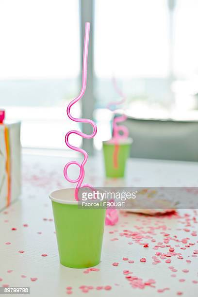 disposable glasses with drinking straws and a birthday present on a table - disposable stock photos and pictures