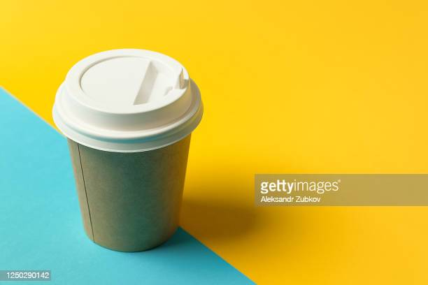 disposable paper cup with lid for coffee and tea on a bright blue and yellow background. coffee-break. - high section stock pictures, royalty-free photos & images
