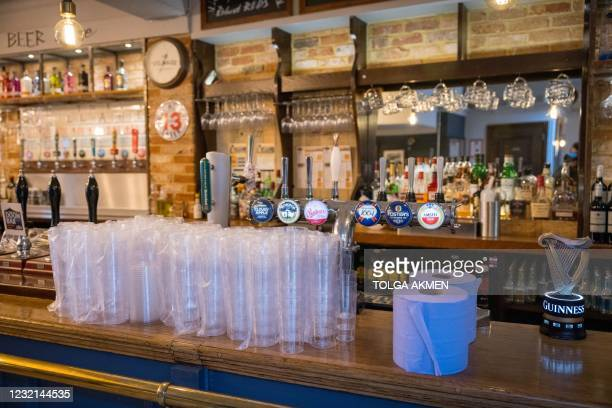 Disposable plastic glasses that will be used for take-away orders, stand on the bar at The Village Pub, in Walthamstow, northeast London on April 6...