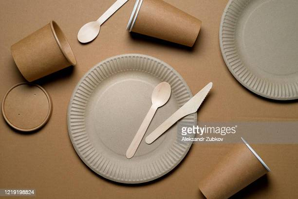 disposable tableware made of bamboo wood and paper on a beige background. the photo is covered with graininess and noise. - 使い捨て製品 ストックフォトと画像