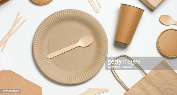 disposable tableware made of bamboo wood and paper on a white background. the photo is covered in graininess and noise. - serviesgoed stockfoto's en -beelden