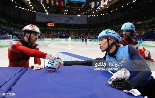 Disqualified Apolo Anton Ohno of the United States shakes hands with bronze medalist FrancoisLouis Tremblay of Canada as he leaves the ice in the...