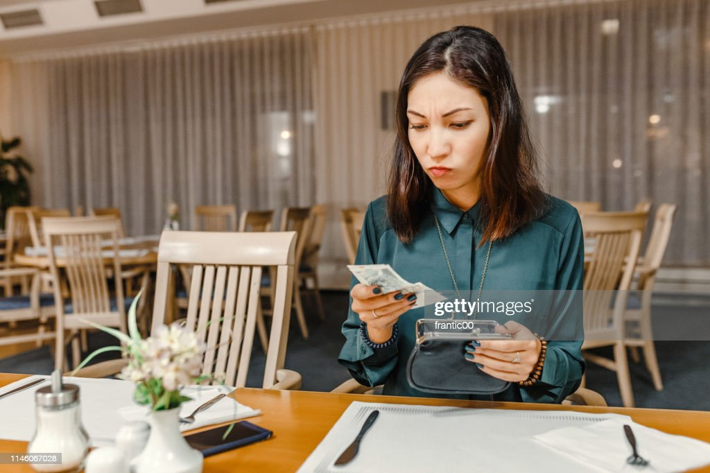 dissatisfied customer woman in the restaurant after dinner gets money out of her wallet to pay the bill, the concept of expensive prices in a cafe : Stock Photo