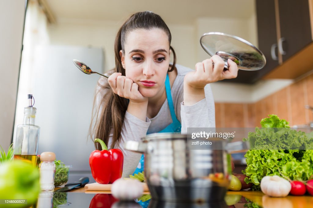 Dissatisfied housewife trying to prepare healthy meal. Cooking learning problems. : Stock Photo