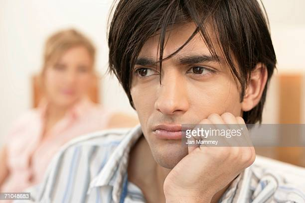 Dissatisfied young man, woman sitting in background