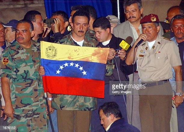 A dissident military officer shows a bloody Venezuelan flag after a shooting at Altamira Plaza December 6 2002 in Caracas Venezuela At least two...