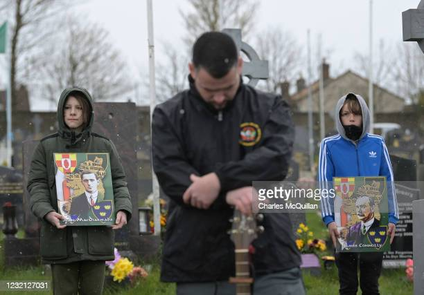 Dissident republican supporters stand in Derry City cemetery during a 1916 wreath laying event as snow falls on April 5, 2021 in Londonderry,...