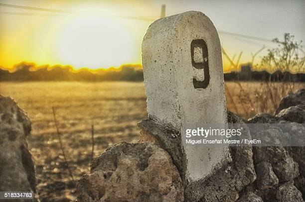 Distance Marker Against Sky During Sunset