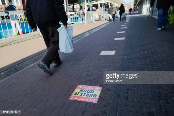 Distance markings are seen on the ground for shoppers at the Hague market one of the largest market in Europe as it reopens it's doors following...
