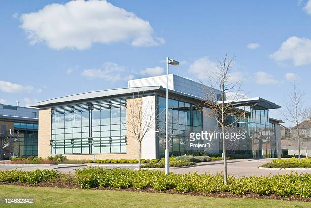 a distance shot of a glass walled office building - community centre stock pictures, royalty-free photos & images