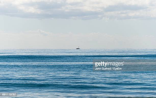 Distance Shot Of Boat In Calm Sea Against Sky