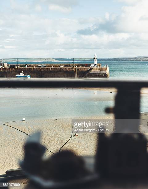 distance shot of lighthouse at calm sea - st ives stock pictures, royalty-free photos & images