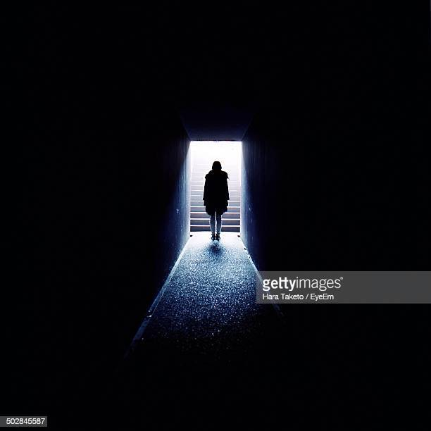 Distance shot of silhouette woman walking in corridor