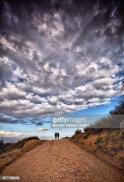 distance shot of two people walking on dirt road - middlebare afstand stockfoto's en -beelden
