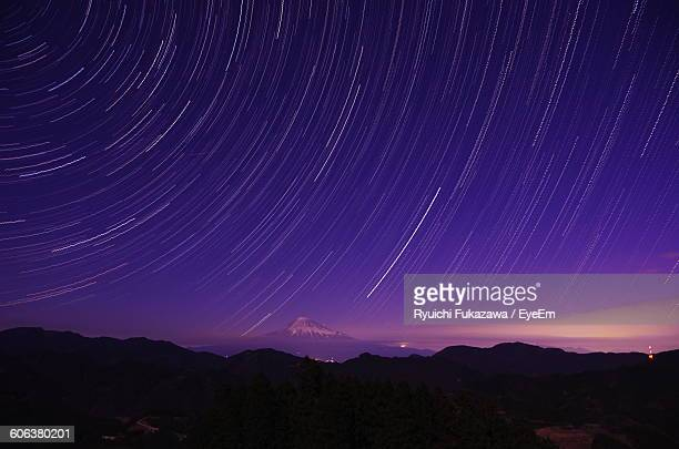 Distance View Of Mt Fuji Against Star Trails At Night