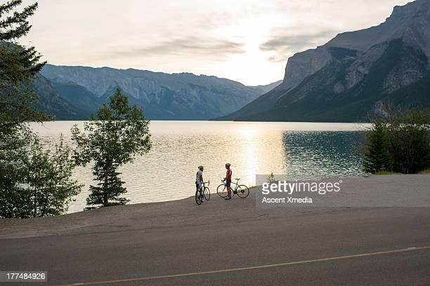 distant bikers converse at edge of mountain road - riva del lago foto e immagini stock