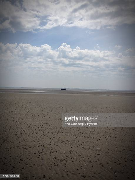 Distant Boat On Beach At Low Tide