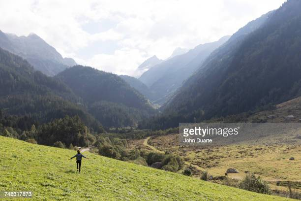 Distant carefree person walking on hill near mountains