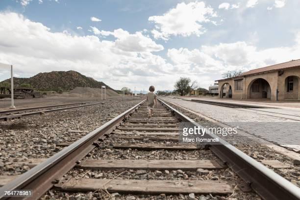 Distant Caucasian boy walking on train track