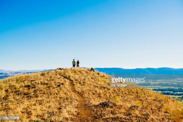 Distant Caucasian couple standing on hill holding hands