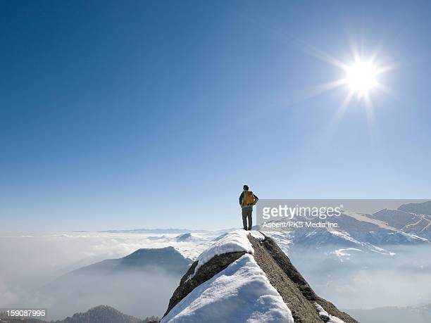 Distant climber stands on mtn summit, looks out