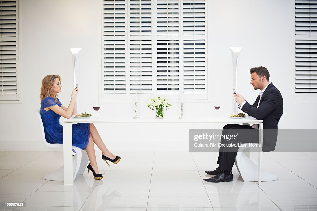 Distant couple having dinner together : Stock Photo