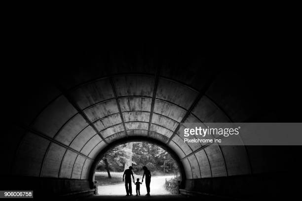 Distant couple in tunnel holding hands with son