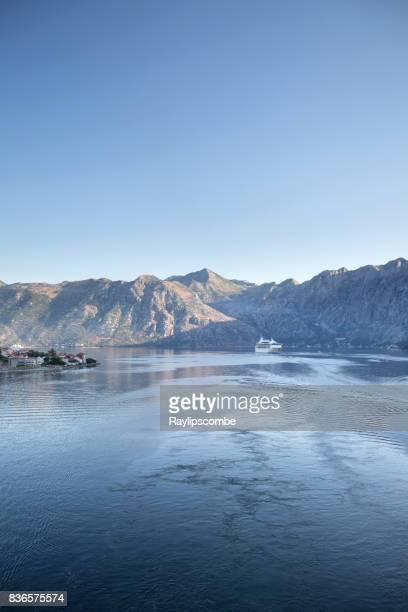 distant cruise ships sailing into the bay of kotor in montenegro on a clear summers morning - kotor bay stock pictures, royalty-free photos & images