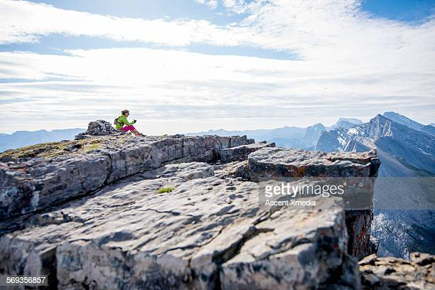 Distant female hiker relaxes on mountain summit