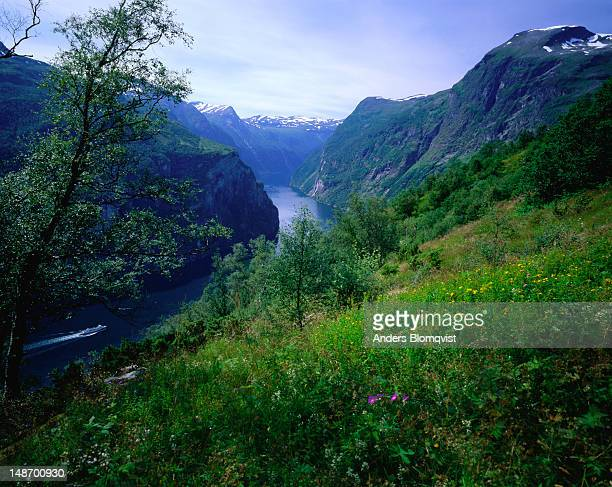 A distant ferry steams towards Seven Sisters waterfall in Geirangerfjord region.