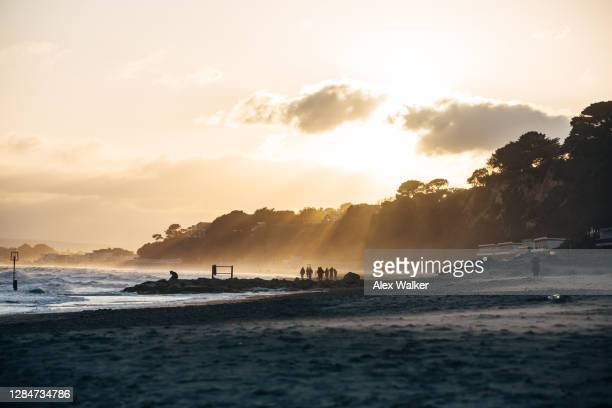 distant figures silhouetted on beach with sun rays - プール市 ストックフォトと画像