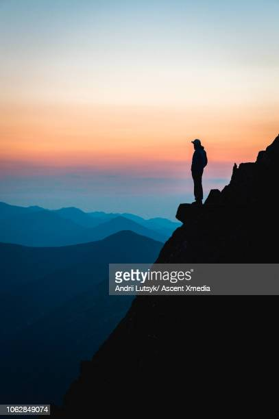 distant hiker looks off to view from mountain promontory - tranquil scene stock pictures, royalty-free photos & images