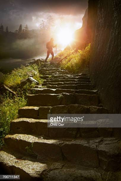 Distant hiker on stone staircase at sunset