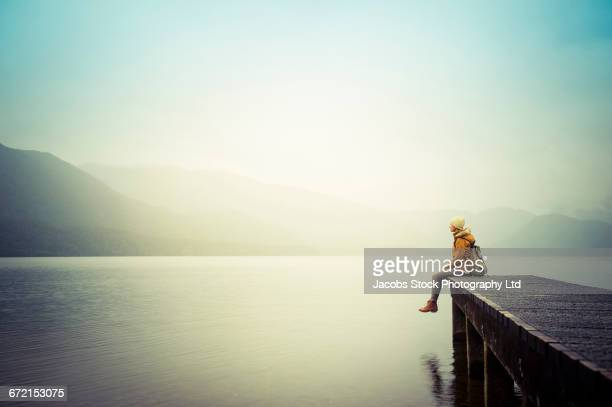 Distant Hispanic woman wearing coat sitting on dock at mountain lake