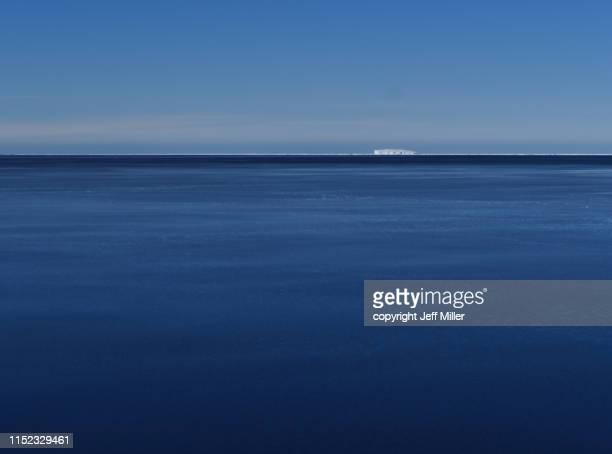 distant iceberg in calm blue sea beneath clear blue sky, southern ocean, antarctica - 南極海 ストックフォトと画像