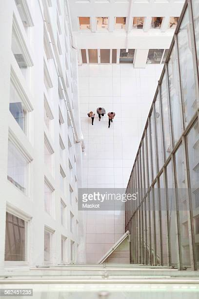 distant image of businesspeople walking in modern office - building atrium stock pictures, royalty-free photos & images