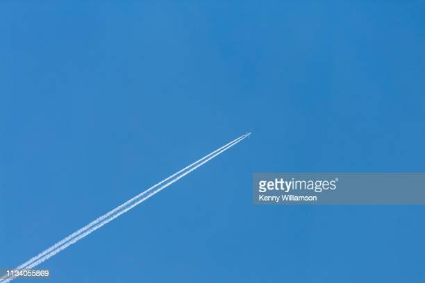 a distant jet aeroplane and vapour trails flying high in a clear blue sky - airplane sky stock pictures, royalty-free photos & images