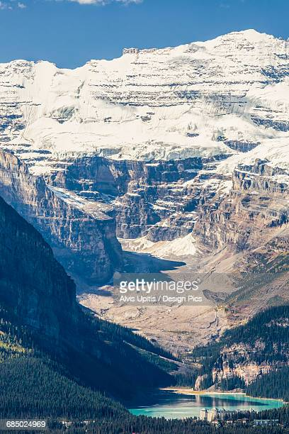 distant lake louise chateau in banff national park, victoria glacier - chateau lake louise stock photos and pictures