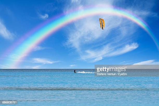 Distant Man Kiteboarding On Sea Under The Rainbow