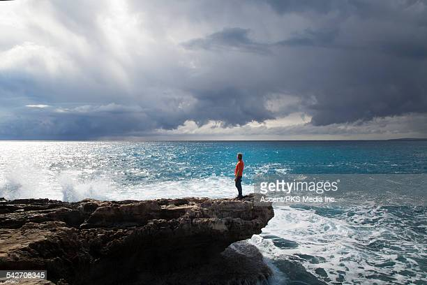 Distant man looks off to sea, from tidal rocks