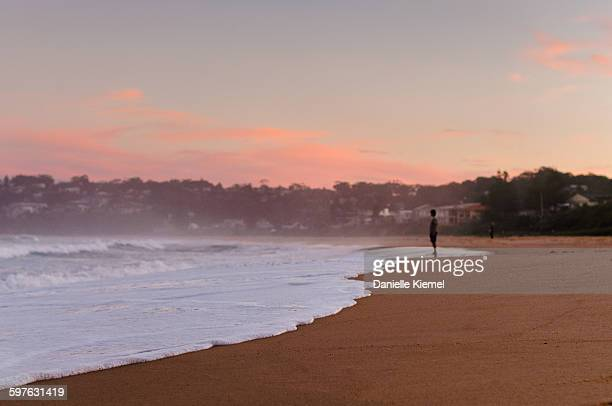 distant man standing on beach at sunset, side view - 沿岸 ストックフォトと画像