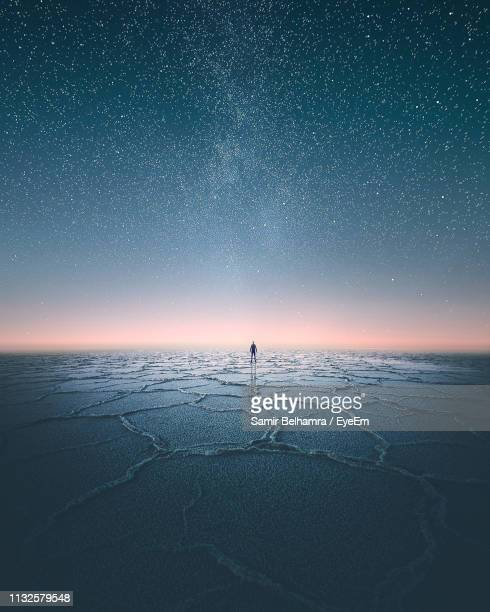 distant man standing on scenic salt flat against starry sky at night - salt flat stock pictures, royalty-free photos & images