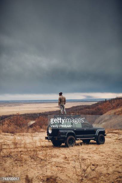 Distant man standing on top of sports utility vehicle over land against cloudy sky, Amur, Russia