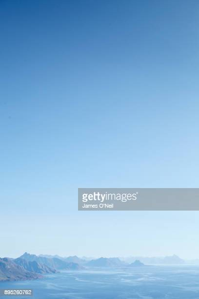 distant mountains and large open blue sky, lofoten, norway - heldere lucht stockfoto's en -beelden